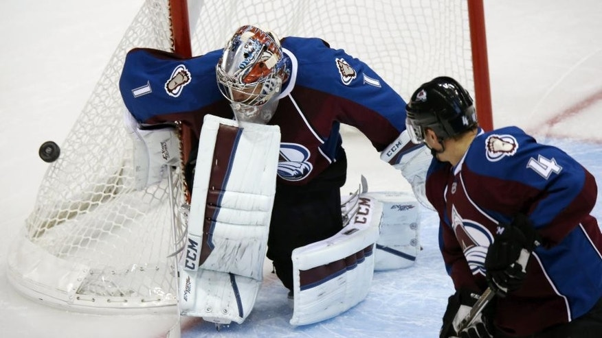 Colorado Avalanche goalie Semyon Varlamov, back, of Russia, deflects shot as defenseman Tyson Barrie looks on against the San Jose Sharks in the second period of an NHL hockey game in Denver on Tuesday, Oct. 28, 2014. (AP Photo/David Zalubowski)