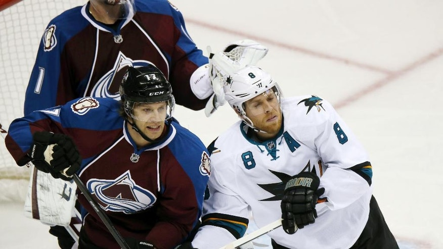 Colorado Avalanche defenseman Brad Stuart, left, battles to clear San Jose Sharks center Joe Pavelski from in front of the net in the second period of an NHL hockey game in Denver on Tuesday, Oct. 28, 2014. (AP Photo/David Zalubowski)