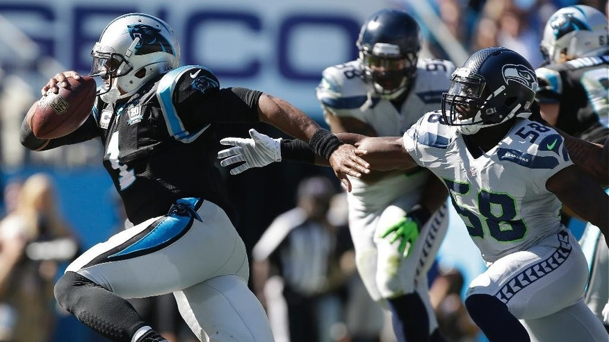 Carolina Panthers quarterback Cam Newton (1) leaves the [pocket rapidly under pressure from from Seattle Seahawks linebacker Kevin Pierre-Louis (58) during the second half of an NFL football game, Sunday, Oct. 26, 2014, in Charlotte. Newton through an interception on the play. (AP Photo/Bob Leverone)