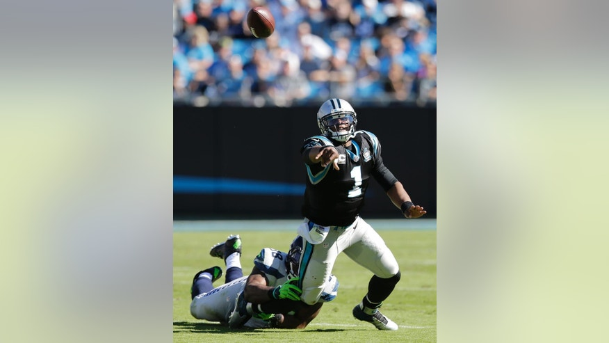 Seattle Seahawks linebacker Kevin Pierre-Louis (58) hits Carolina Panthers quarterback Cam Newton (1) during the second half of an NFL football game, Sunday, Oct. 26, 2014, in Charlotte. Newton gave up an interception to Seattle Seahawks defensive back Marcus Burley on the play. (AP Photo/Chuck Burton)