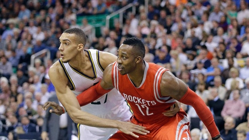 Utah Jazz's Rudy Gobert, left, guards Houston Rockets' Dwight Howard (12) in the first half during an NBA basketball game Wednesday, Oct. 29, 2014, in Salt Lake City. (AP Photo/Rick Bowmer)