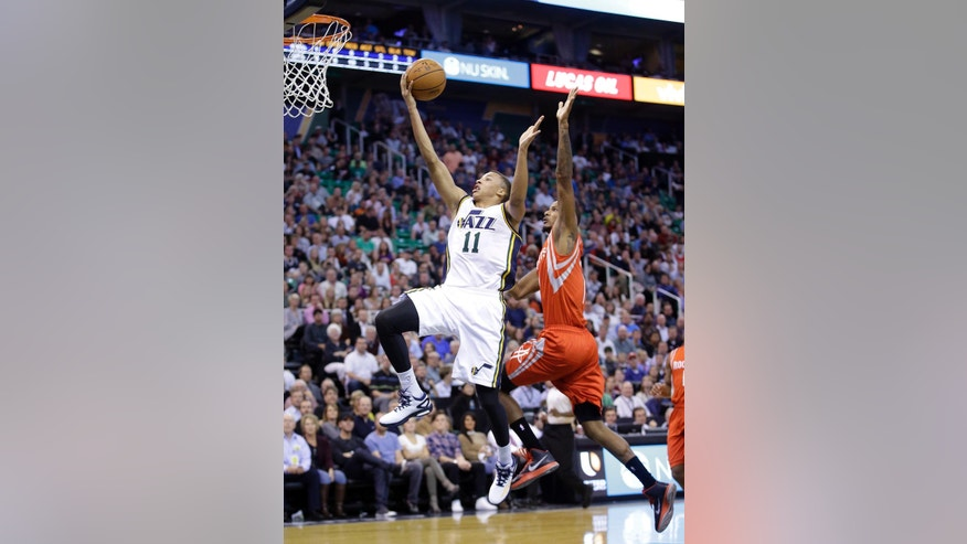 Utah Jazz's Dante Exum (11) lays the ball up as Houston Rockets' Trevor Ariza, right, defends in the first half of an NBA basketball game in Salt Lake City on Wednesday, Oct. 29, 2014. (AP Photo/Rick Bowmer)