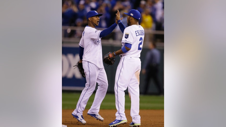 Kansas City Royals Jarrod Dyson, left, high fives Alcides Escobar after Game 6 of baseball's World Series Tuesday, Oct. 28, 2014, in Kansas City, Mo. The Royals defeated the Giants 10-0 to tie the series at 3-3.(AP Photo/Charlie Neibergall)