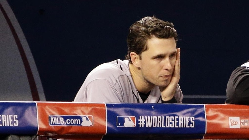 San Francisco Giants' Buster Posey watches from the dugout during the second inning of Game 6 of baseball's World Series against the Kansas City Royals Tuesday, Oct. 28, 2014, in Kansas City, Mo. (AP Photo/David J. Phillip)