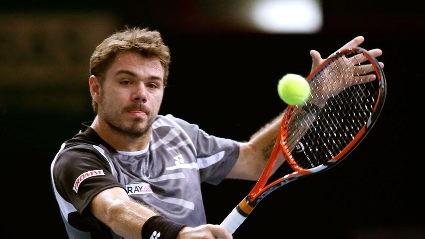 Stanislas Wawrinka of Switzerland, returns the ball to Dominic Thiem of Austria, during their second round match at the ATP World Tour Masters tennis tournament at Bercy stadium in Paris, France, Wednesday, Oct. 29, 2014. (AP Photo/Michel Euler)