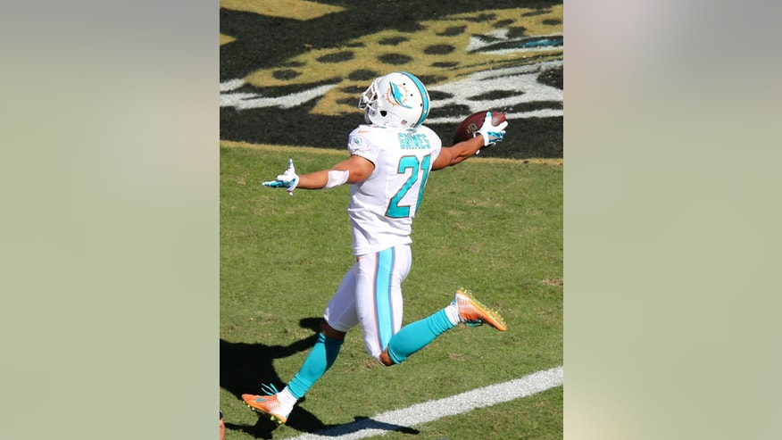 FILE - In this Oct. 26, 2014, file photo, Miami Dolphins cornerback Brent Grimes (21) celebrates as he scores a touchdown on a pass interception against the Jacksonville Jaguars during the second half of an NFL football game in Jacksonville, Fla. With a succession of big takeaways, including two touchdowns last week, the Miami Dolphins are on pace to set an NFL record for the most yards per interception in a season. (AP Photo/Gary McCullough, File)