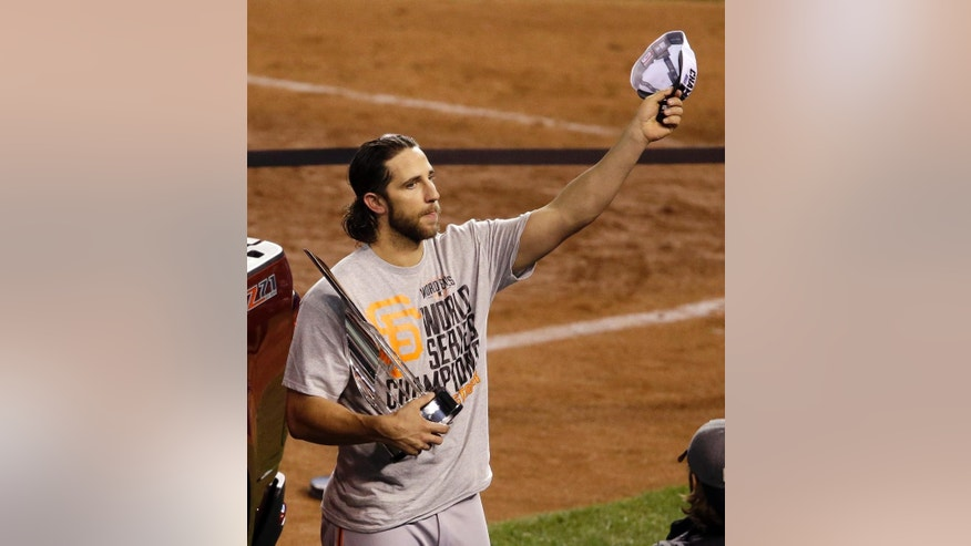 San Francisco Giants pitcher Madison Bumgarner celebrates with the MVP trophy    after Game 7 of baseball's World Series against the Kansas City Royals Wednesday, Oct. 29, 2014, in Kansas City, Mo. The Giants won 3-2 to win the series. (AP Photo/Orlin Wagner)