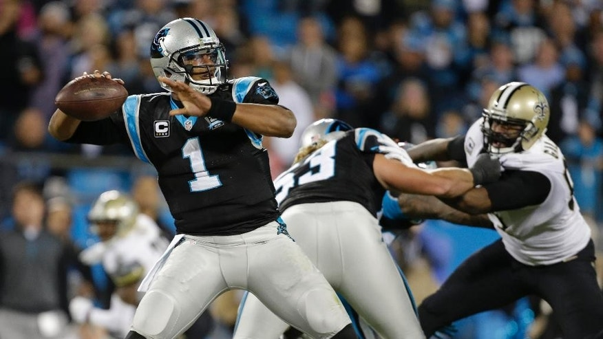 Carolina Panthers' Cam Newton (1) looks to pass against the New Orleans Saints in the first half of an NFL football game in Charlotte, N.C., Thursday, Oct. 30, 2014. (AP Photo/Bob Leverone)