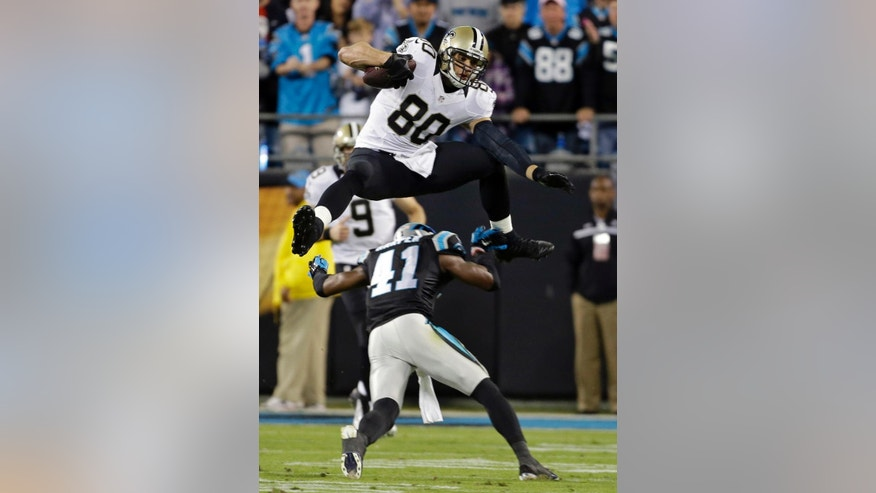 New Orleans Saints' Jimmy Graham (80) leaps over Carolina Panthers' Roman Harper (41) in the first half of an NFL football game in Charlotte, N.C., Thursday, Oct. 30, 2014. (AP Photo/Bob Leverone)
