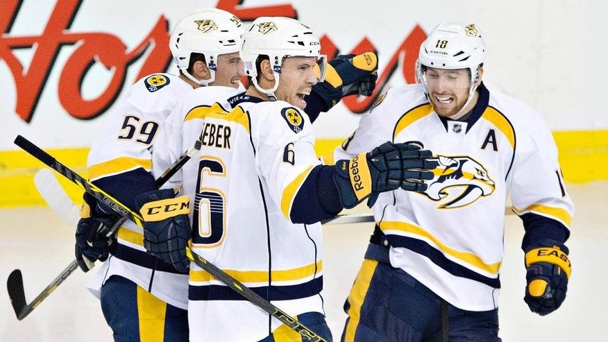 Nashville Predators' Roman Josi (59), Shea Weber (6) and James Neal (18) celebrate a goal against the Edmonton Oilers during the third period of an NHL hockey game, Wednesday, Oct. 29, 2014 in Edmonton, Alberta. (AP Photo/The Canadian Press, Jason Franson)