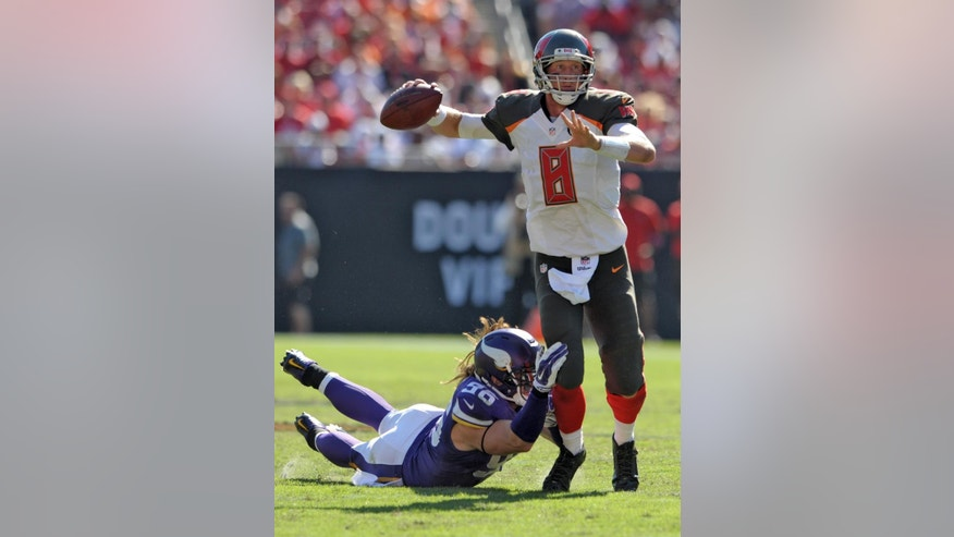 Tampa Bay Buccaneers quarterback Mike Glennon (8) is tripped up by Minnesota Vikings defensive end Brian Robison (96) during the fourth quarter of an NFL football game, Sunday, Oct. 26, 2014, in Tampa, Fla. (AP Photo/Steve Nesius)