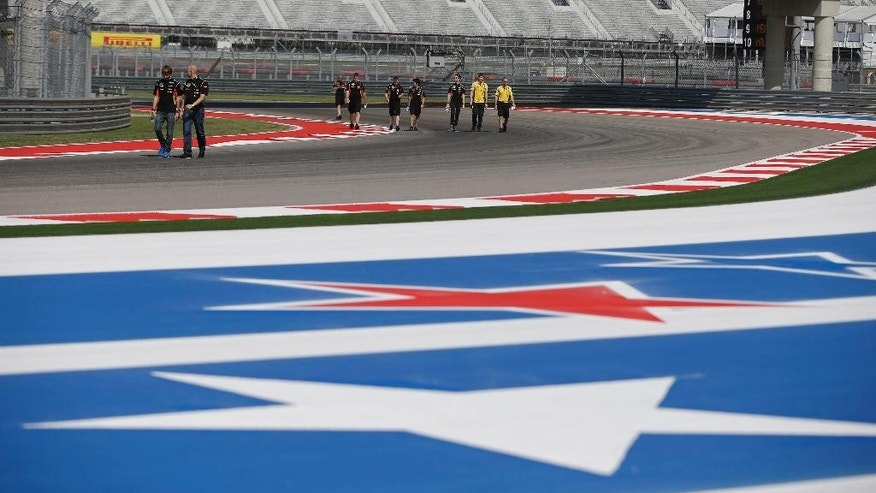 Members of the Lotus Formula One teams walk the track before the Formula One U.S. Grand Prix auto race at the Circuit of the Americas, Thursday, Oct. 30, 2014, in Austin, Texas. (AP Photo/Darron Cummings)