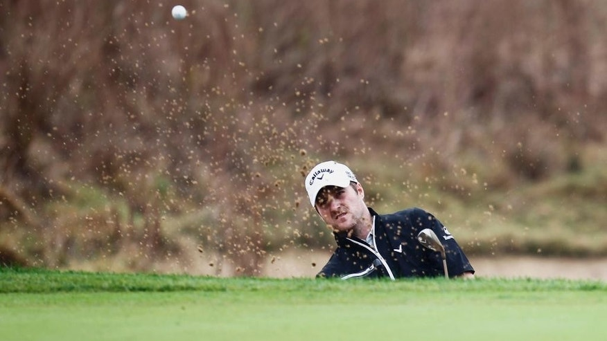 Marc Warren of Scotland hits from a bunker on the 14th green during the first round of the BMW Masters golf tournament at the Lake Malaren Golf Club in Shanghai, China Thursday Oct.30, 2014. (AP Photo)