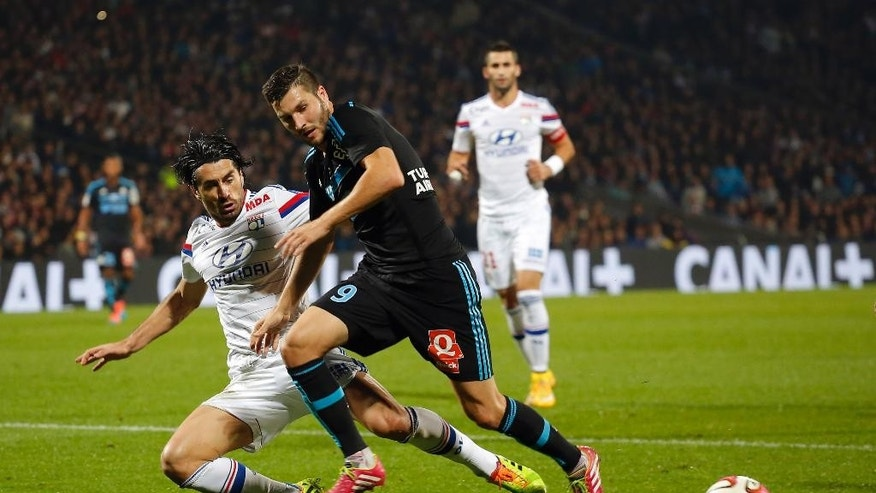 Marseille's Andre-Pierre Gignac, right, in action with Lyon's Milan Bisevac, left, during their French League One soccer match at Gerland stadium, in Lyon, central France, Sunday, Oct. 26, 2014. (AP Photo/Laurent Cipriani)