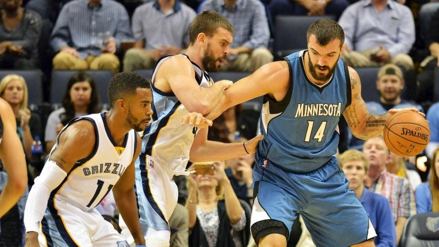 Minnesota Timberwolves center Nikola Pekovic (14) dribbles against Memphis Grizzlies center Marc Gasol, center, and Memphis Grizzlies guard Mike Conley (11) in the first half of an NBA basketball game Wednesday, Oct. 29, 2014, in Memphis, Tenn. (AP Photo/Brandon Dill)