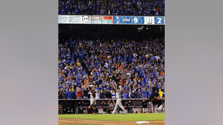 San Francisco Giants starting pitcher Madison Bumgarner, right, and catcher Buster Posey celebrate 3-2 win against the Kansas City Royals in Game 7 of baseball's World Series Wednesday, Oct. 29, 2014, in Kansas City, Mo. (AP Photo/David J. Phillip)