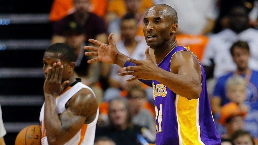 Los Angeles Lakers guard Kobe Bryant reacts to a call as Phoenix Suns guard Eric Bledsoe holds his eye during the first half of an NBA basketball game, Wednesday, Oct. 29, 2014, in Phoenix. (AP Photo/Matt York)