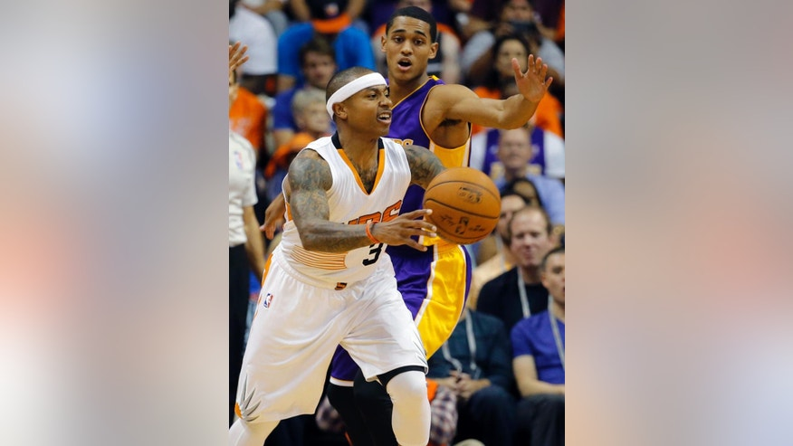 Phoenix Suns guard Isaiah Thomas, front, passes against the Los Angeles Lakers during the first half of an NBA basketball game, Wednesday, Oct. 29, 2014, in Phoenix. (AP Photo/Matt York)