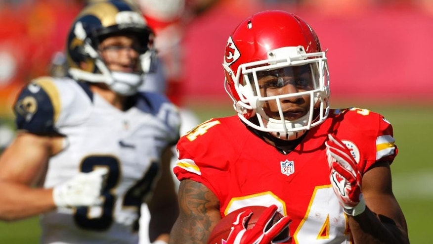 Kansas City Chiefs running back Knile Davis (34) is chased by St. Louis Rams running back Chase Reynolds (34) as he scores a touchdown on a kickoff return in the second half of an NFL football game in Kansas City, Mo., Sunday, Oct. 26, 2014. (AP Photo/Colin E. Braley)