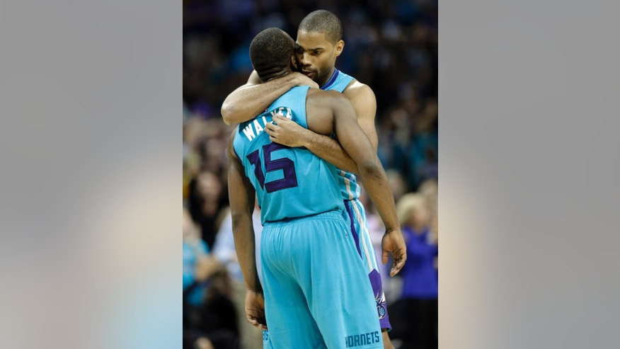 Charlotte Hornets' Gary Neal, back, hugs Kemba Walker, front, after Walker's game-winning basket against the Milwaukee Bucks during overtime of an NBA basketball game in Charlotte, N.C., Wednesday, Oct. 29, 2014. The Hornets won 108-106 in overtime. (AP Photo/Chuck Burton)
