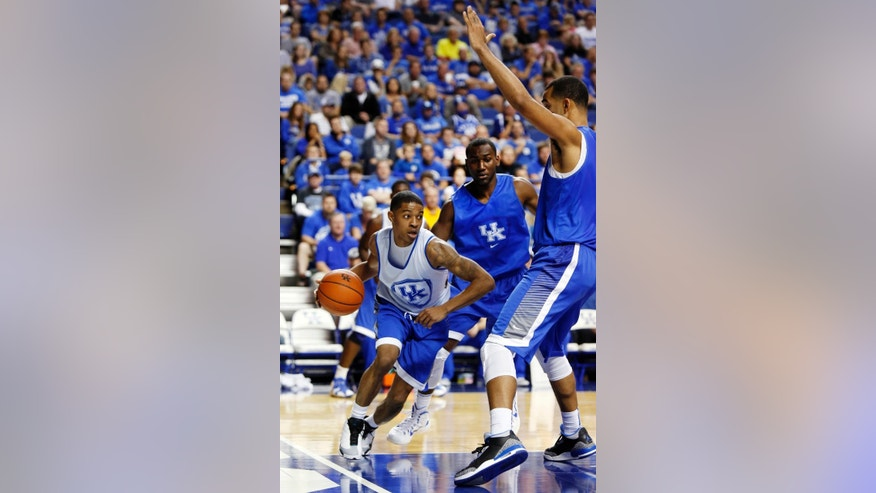The White squads' Tyler Ulis, from left, looks for an opening on the Blue squads' Dominique Hawkins and Trey Lyles during Kentucky's intrasquad NCAA college basketball scrimmage, Monday, Oct. 27, 2014, in Lexington, Ky. (AP Photo/James Crisp)