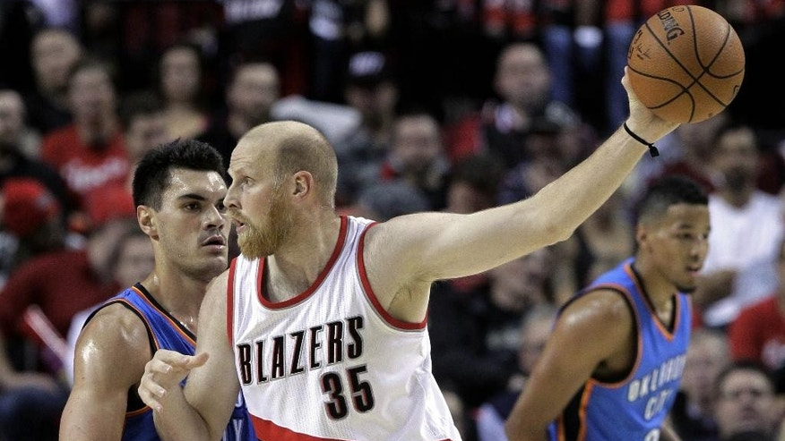 Portland Trail Blazers center Chris Kaman, right, holds the ball out of reach as he looks to pass while Oklahoma City Thunder center Steve Adams, from New Zealand,  defends during the first half of an NBA basketball game in Portland, Ore., Wednesday, Oct. 29, 2014.(AP Photo/Don Ryan)