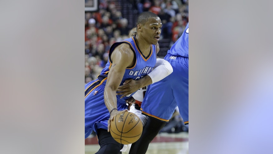 Oklahoma City Thunder guard Russell Westbrook, left, drives to the hoop as Portland Trail Blazers guard Damian Lillard reaches in from behind during the first half of an NBA basketball game in Portland, Ore., Wednesday, Oct. 29, 2014.(AP Photo/Don Ryan)