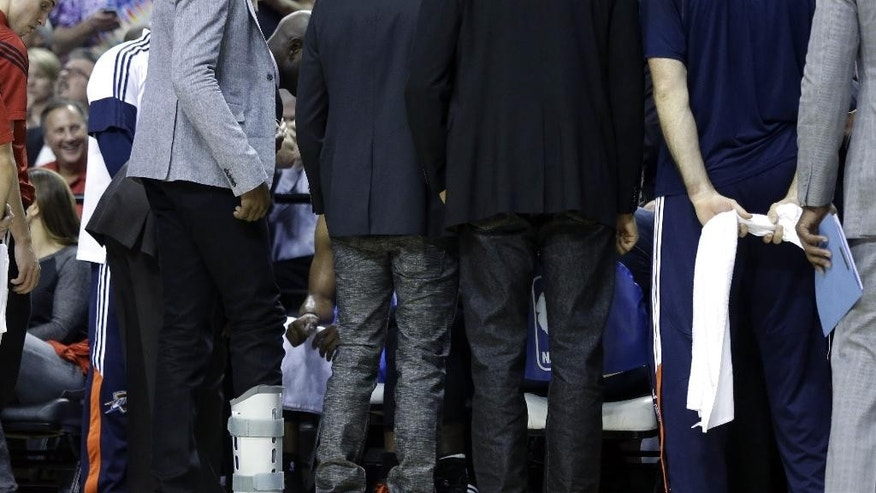 Oklahoma City Thunder forward Kevin Durant stands with a cast on his foot  during a break in an NBA basketball game against the Portland Trail Blazers in Portland, Ore., Wednesday, Oct. 29, 2014. Durant broke his right foot earlier this month and will most likely be sidelined into December.(AP Photo/Don Ryan)