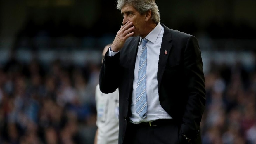 Manchester City's manager Manuel Pellegrini holds his hand up to his face during the English Premier League soccer match between West Ham and Manchester City at Upton Park stadium in London, Saturday, Oct. 25, 2014. (AP Photo/Matt Dunham)