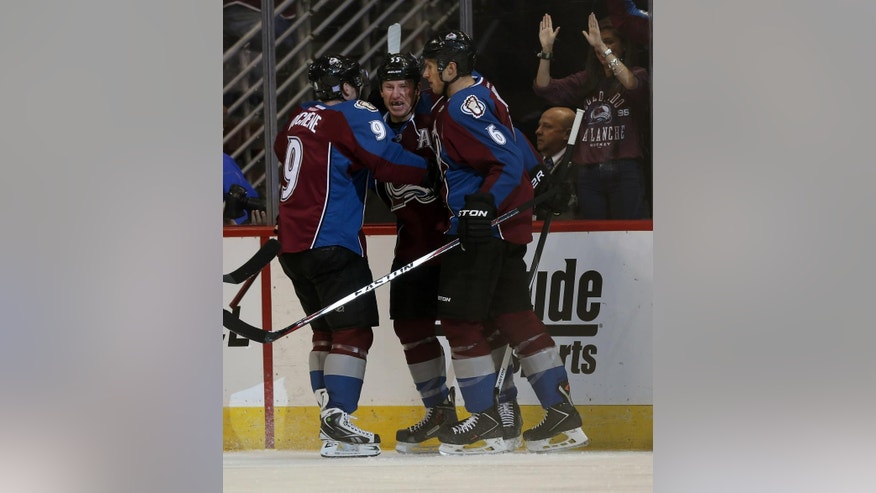 Colorado Avalanche left wing Cody McLeod, center, celebrates scoring a goal with teammates Matt Duchene, left, and Erik Johnson against the New York Islanders in the first period of an NHL hockey game in Denver, Thursday, Oct. 30, 2014. (AP Photo/David Zalubowski)