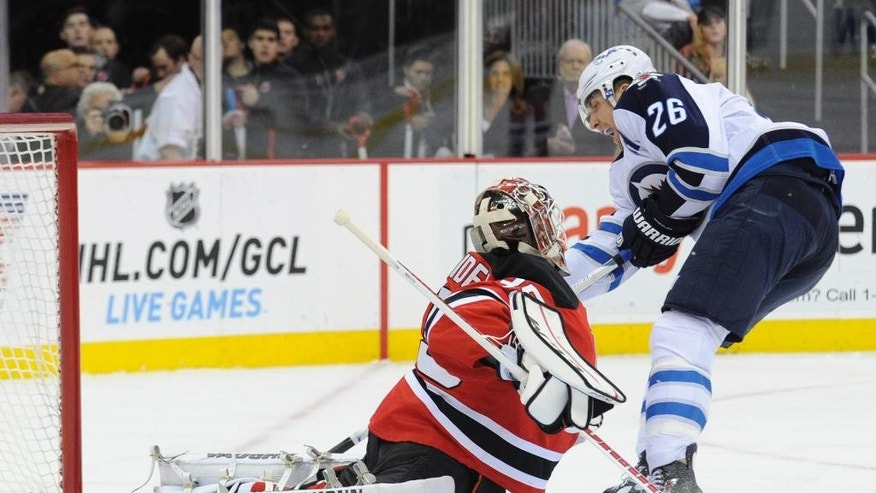 Winnipeg Jets' Blake Wheeler, right, scores a goal past New Jersey Devils goaltender Cory Schneider during the first period of an NHL hockey game Thursday, Oct. 30, 2014, in Newark, N.J. (AP Photo/Bill Kostroun)
