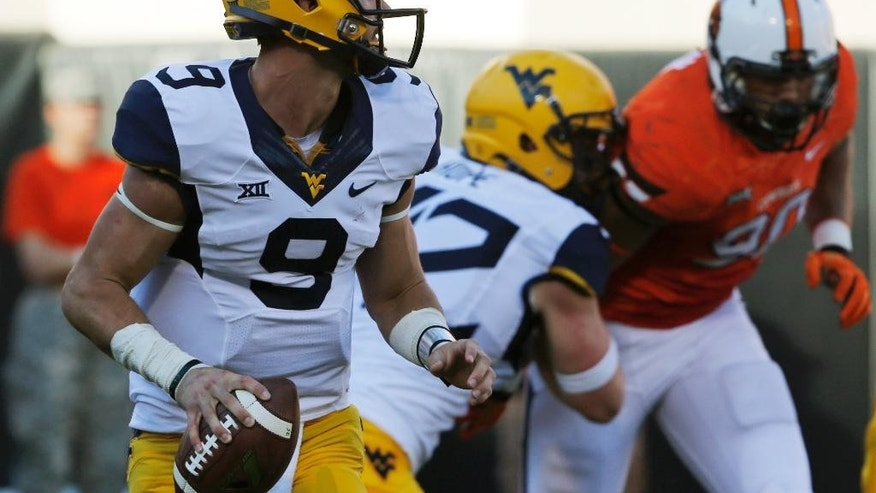 West Virginia quarterback Clint Trickett (9) looks for a receiver in the fourth quarter of an NCAA college football game against Oklahoma State in Stillwater, Okla., Saturday, Oct. 25, 2014. West Virginia won 34-10. (AP Photo/Sue Ogrocki)