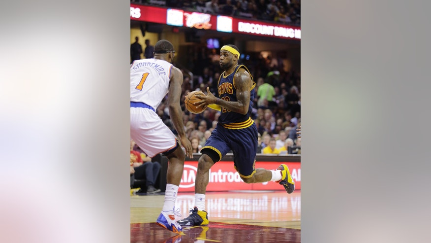 Cleveland Cavaliers' LeBron James, right, drives to the basket against New York Knicks' Amare Stoudemire (1) in the first quarter of an NBA basketball game Thursday, Oct. 30, 2014, in Cleveland. (AP Photo/Tony Dejak)