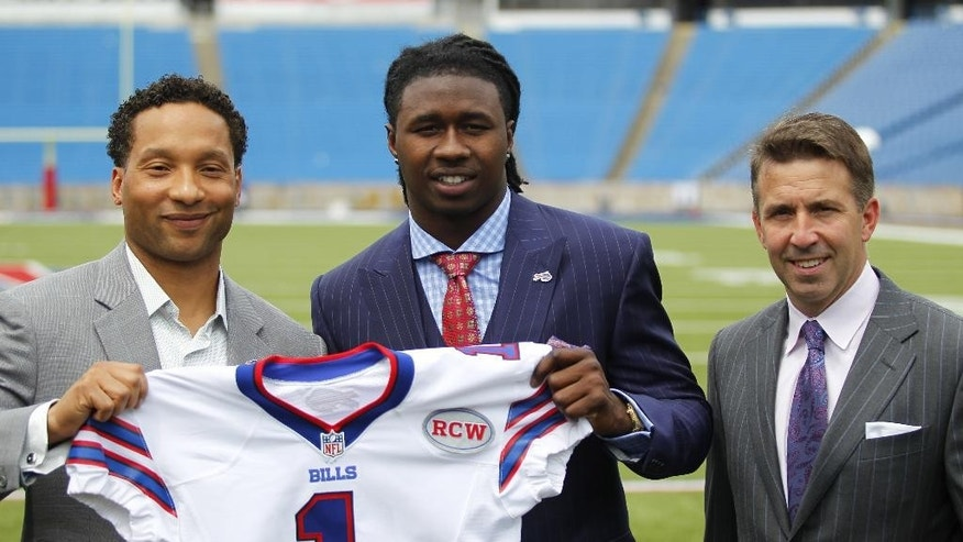 FILE - In this May 9, 2014, file photo, Buffalo Bills first-round draft pick Sammy Watkins, center, poses for photos with  general manager Doug Whaley, left, and president/CEO Russ Brandon at Ralph Wilson Stadium in Orchard Park, N.Y. The RCW patch honors the team's late owner, Ralph C. Wilson, Jr. (AP Photo/Bill Wippert, File)