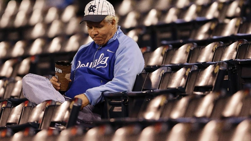 A Kansas City Royals fan sits in the stands after Game 7 of baseball's World Series against the San Francisco Giants, Wednesday, Oct. 29, 2014, in Kansas City, Mo. The Giants won 3-2 to win the series.(AP Photo/Jeff Roberson)