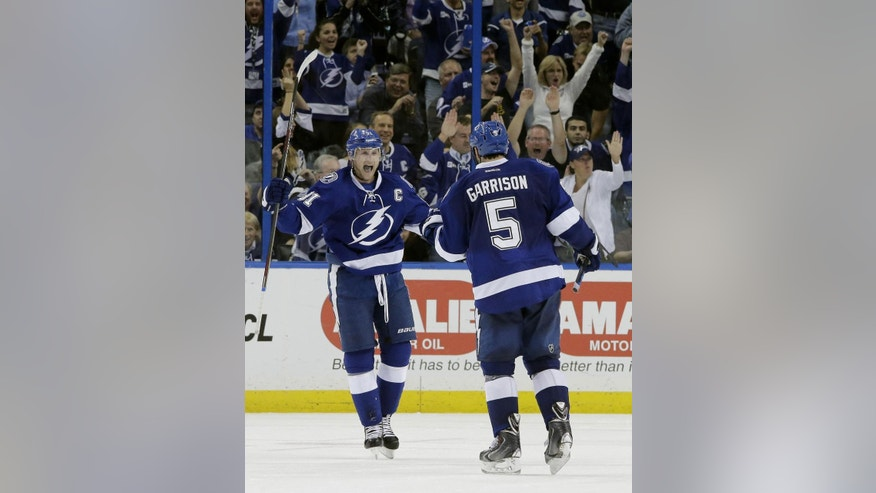 Tampa Bay Lightning center Steven Stamkos (91) celebrates with defenseman Jason Garrison (5) after Garrison scored a goal against the Philadelphia Flyers during the third period of an NHL hockey game Thursday, Oct. 30, 2014, in Tampa, Fla. The Lightning won the game 4-3. (AP Photo/Chris O'Meara)