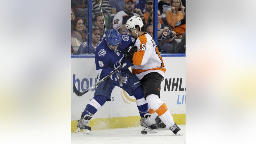 Tampa Bay Lightning center Tyler Johnson (9) and Philadelphia Flyers defenseman Michael Del Zotto (15) battle for a loose puck during the second period of an NHL hockey game Thursday, Oct. 30, 2014, in Tampa, Fla. (AP Photo/Chris O'Meara)