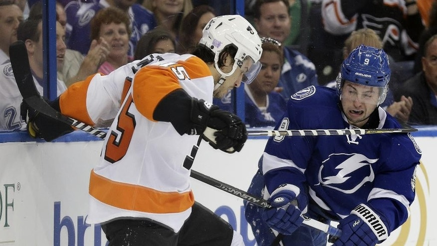 Tampa Bay Lightning center Tyler Johnson (9) and Philadelphia Flyers defenseman Michael Del Zotto (15) trade high sticks during the second period of an NHL hockey game Thursday, Oct. 30, 2014, in Tampa, Fla. (AP Photo/Chris O'Meara)