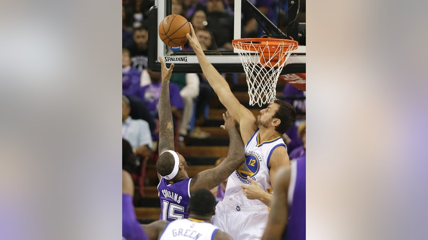 Golden State Warriors center Andrew Bogut, right, of Australia, blocks the shot of Sacramento Kings center DeMarcus Cousins during the first quarter of an NBA basketball game in Sacramento, Calif., Wednesday, Oct. 29 2014. (AP Photo/Rich Pedroncelli)