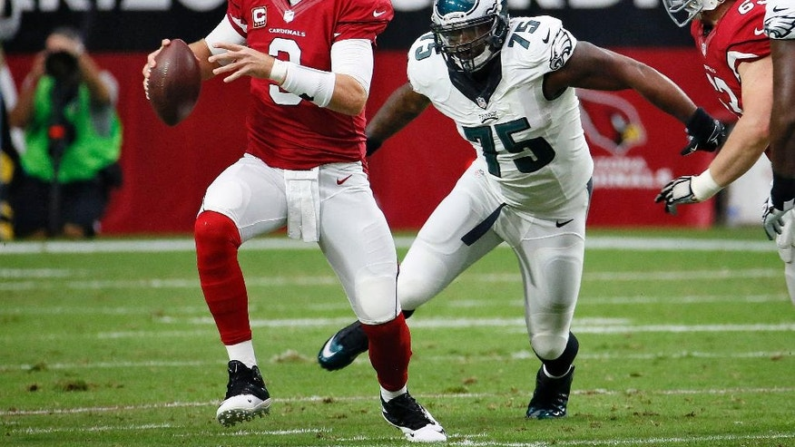 Arizona Cardinals quarterback Carson Palmer (3) scrambles as Philadelphia Eagles defensive end Vinny Curry (75) pursues during the first half of an NFL football game, Sunday, Oct. 26, 2014, in Glendale, Ariz. (AP Photo/Matt York)