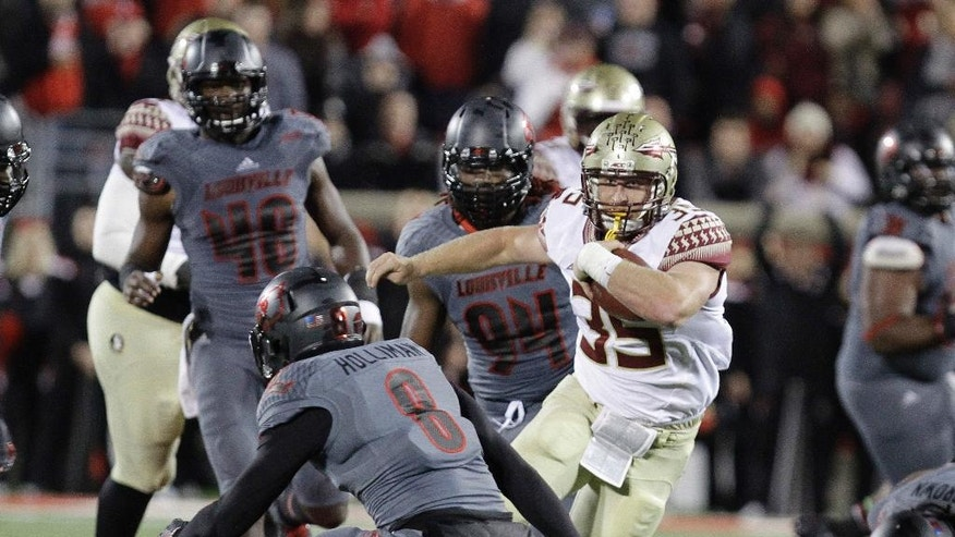 Florida State's Nick O'Leary, right, attempts to run past the defense of Louisville's Gerod Holliman (8) during the second half of their NCAA college football game in Louisville, Ky., Thursday, Oct. 30, 2014. Florida State defeated Louisville 42-31. (AP Photo/Garry Jones)