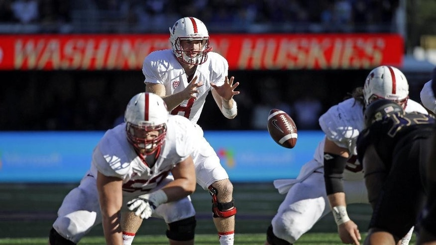 FILE - In this Sept. 27, 2014, file photo, Stanford quarterback Kevin Hogan takes a snap against Washington in an NCAA football game in Seattle. It has become common for teams to line up in shotgun formation on short-yardage plays, forgoing the possibility of a quarterback sneak for the ability to use the entire playbook. (AP Photo/Elaine Thompson, File)