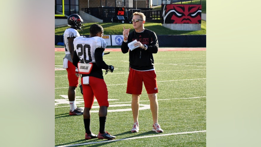 In this Oct. 17, 2014 photo, first-year Arkansas State coach Blake Anderson discusses a play with freshman Brandon Cox during a practice in Jonesboro, Ark. Anderson is the fifth head coach in as many seasons for the Red Wolves, who are trying to win a share of the Sun Belt Conference championship for the fourth time in four years this year. (AP Photo/Kurt Voigt)