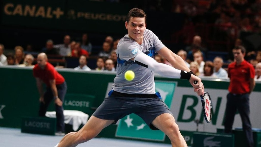 Milos Raonic of Canada, returns the ball to Roger Federer of Switzerland during their quarterfinal match at the ATP World Tour Masters tennis tournament at Bercy stadium in Paris, France, Friday, Oct. 31, 2014. Raonic won 7-6, 7-5.  (AP Photo/Michel Euler)