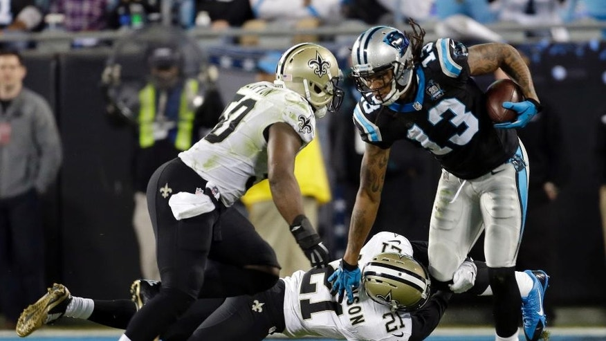Carolina Panthers' Kelvin Benjamin (13) is tackled by New Orleans Saints' Patrick Robinson (21) and Curtis Lofton (50) in the first half of an NFL football game in Charlotte, N.C., Thursday, Oct. 30, 2014. (AP Photo/Bob Leverone)