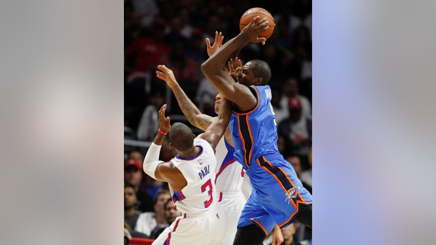 Oklahoma City Thunder forward Serge Ibaka, right, battles Los Angeles Clippers guard Chris Paul (3) and forward Matt Barnes, center, for the loose ball during the first half of an NBA basketball game in Los Angeles, Thursday, Oct. 30, 2014. (AP Photo/Alex Gallardo)
