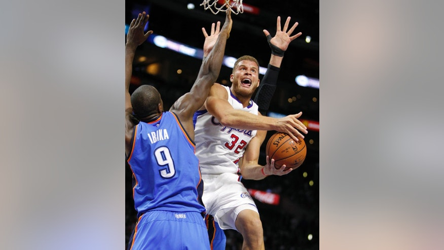 Los Angeles Clippers forward Blake Griffin (32) goes up for a shot against Oklahoma City Thunder forward Serge Ibaka (9) during the first half of an NBA basketball game in Los Angeles, Thursday, Oct. 30, 2014. (AP Photo/Alex Gallardo)
