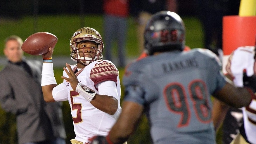 Florida State's Jameis Winston, left, attempts a pass over the pressure of Louisville's Sheldon Rankins during the first half of their NCAA college football game in Louisville, Ky., Thursday, Oct. 30, 2014. (AP Photo/Timothy D. Easley)