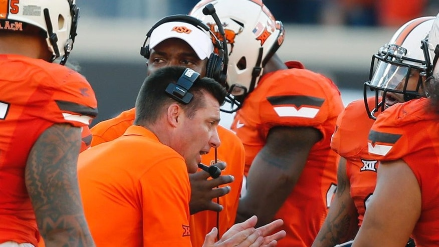 Oklahoma State coach Mike Gundy talks with his team during a timeout in the fourth quarter of an NCAA college football game against West Virginia in Stillwater, Okla., Saturday, Oct. 25, 2014. West Virginia won 34-10. (AP Photo/Sue Ogrocki)