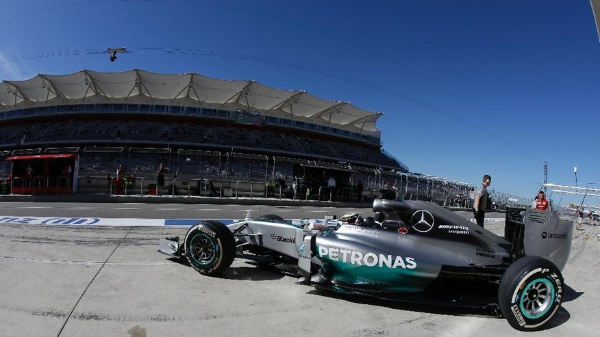 Mercedes driver Lewis Hamilton, of Britain, pulls out of the garage during the first practice session for the Formula One U.S. Grand Prix auto race at the Circuit of the Americas, Friday, Oct. 31, 2014, in Austin, Texas. (AP Photo/Darron Cummings)